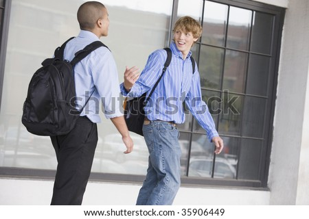Two teenage boys wearing backpack and talking to each other