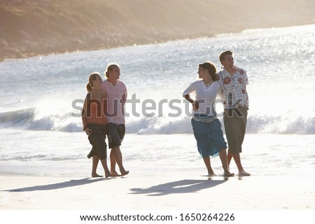 Two teenage couples (17-19) walking on beach near water's edge, front view