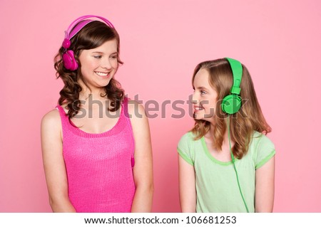 Two teenage friends enjoying music together and looking at the other