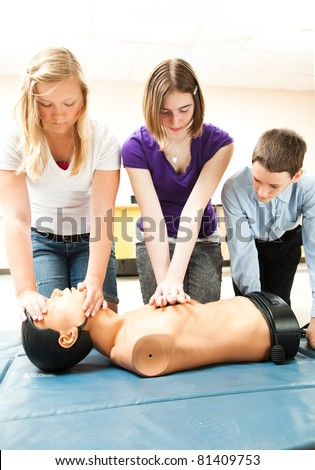 Two teenage girls and a boy practicing CPR life saving in school.