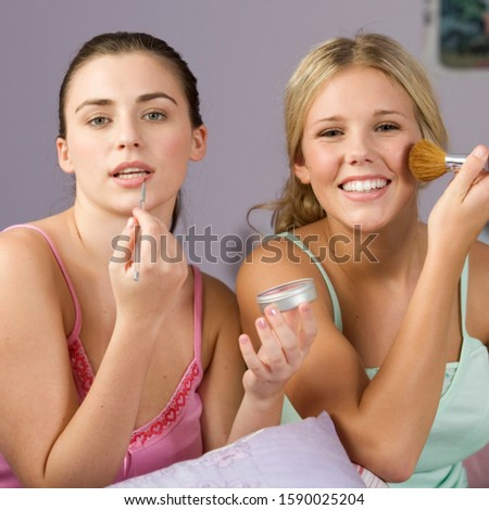 Two teenage girls applaying make up