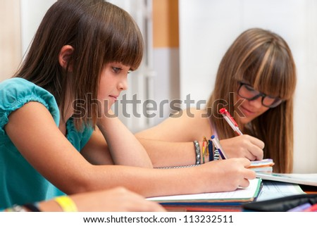 Two teenage girls doing homework at desk.