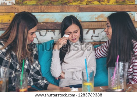 Two teenage girls friends supporting and consoling crying young woman - friendship concept with young millennial girls at restaurant talking about couple problems – relationship problems of teenagers #1283769388