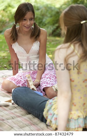 Two teenage girls having a picnic in the park.