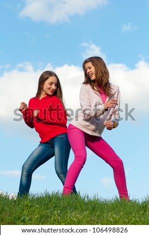 Two teenage girls having fun outdoor on sunny spring day.