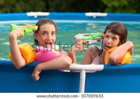 Two teenage girls having fun with their childhood toys in the home swimming pool.