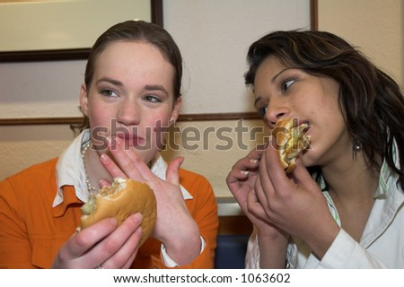 Two teenage girls in a fast food restaurant eating hamburgers