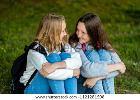 Two teenage girls. In the summer of the city park. They sit on the grass. Behind backpacks. The concept of school friendship. Emotion of happiness pleasure pleasure. #1121281508