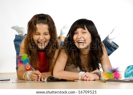 Two teenage girls laying on the floor and laughing. They're writing or doing homework.