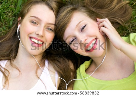 Two teenage girls listening to MP3 player