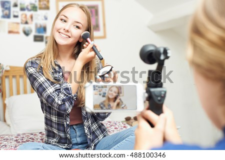 Two Teenage Girls Recording Beauty Blog In Bedroom