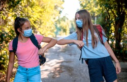 Two Teenage Girls say hello touching hands elbow meeting in the Park on the way to School. New handshake due to Coronavirus pandemic safety protective behavior