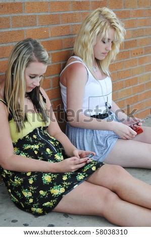 Two teenage girls sitting next to a brick wall texting on their mobile cellphones.
