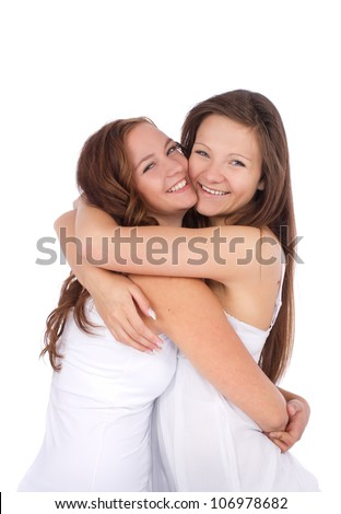 Two teenage girls smiling and hugging over white background - stock photo