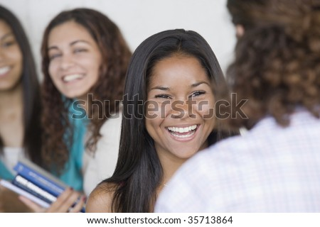 Two teenage girls talking to each other with two others in background.