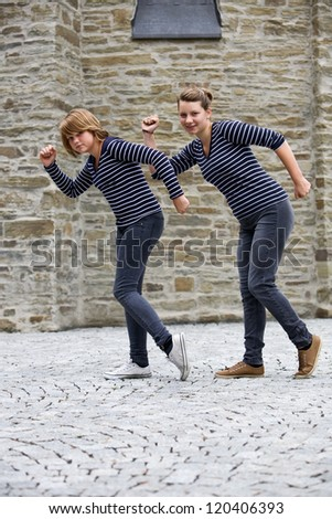 Two teenage girls wearing the same dress and dancing outdoors