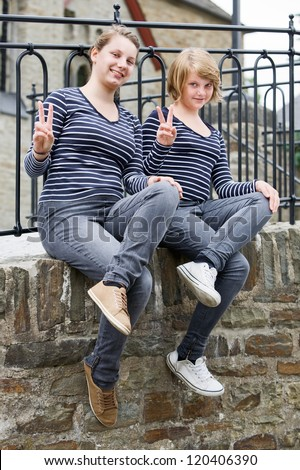 Two teenage girls wearing the same dress and showing peace sign