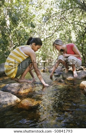 Two teenage girls (16-17 years) squatting on stone by stream in forest, hands in water