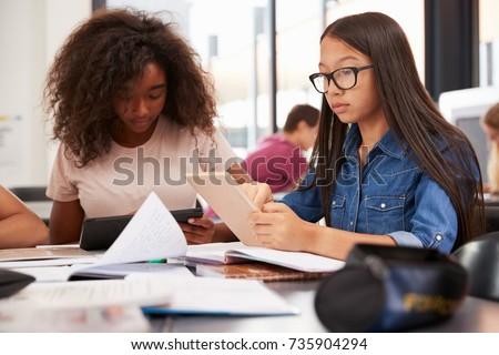 Two teenage schoolgirls using tablet computers in class