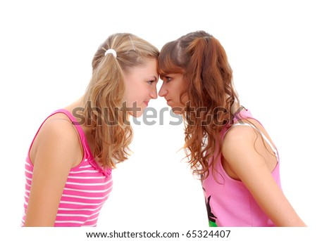 two teenage sisters staring at each other isolated on white