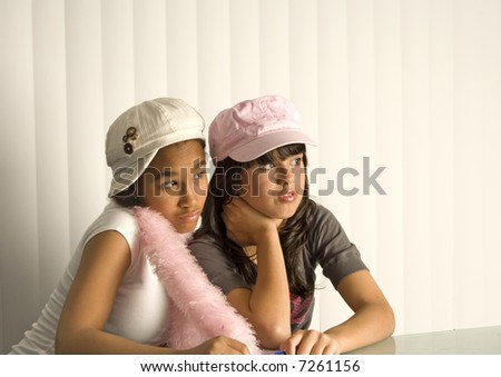 Two teenager friends sitting side by side