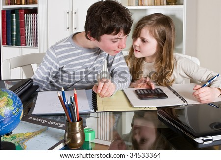 Two teenager kids helping each other with their homework