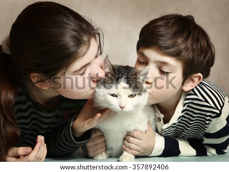 two teenager siblings boy and girl kiss siberian fat cat on cheeks close up indoors portrait