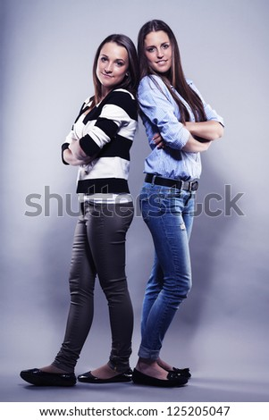 two teenager standing back to back on gray background