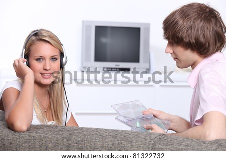 Two teenagers at home listening to music