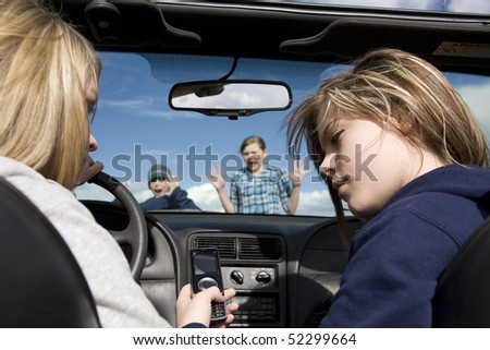 Two teenagers being distracted by a cell phone text, instead of watching the road.  They are about to hit a boy and girl crossing infront of the car.