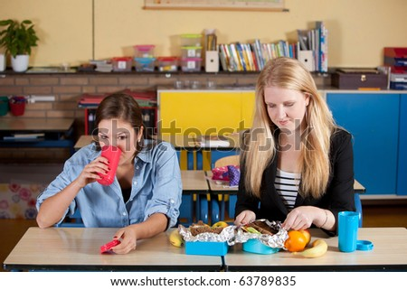Two teenagers having a healthy school lunch in the classroom