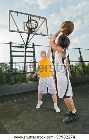 Two teenagers playing basketball at the street playground