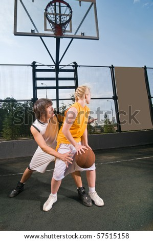Two teenagers playing streetball with boy defending against girl