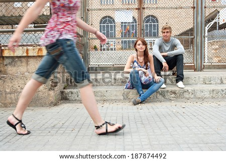 Two teenagers relaxing in a college campus with another young woman body figure walking passed the building. Students outdoors lifestyle.