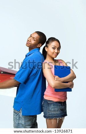 Two teenagers standing back to back holding notebooks are smiling. Vertically framed photograph