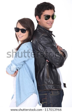 Two teenagers stood back to back wearing sunglasses