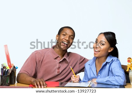 Two Teens are are seated at a desk taking notes and smiling. There are pencils, folders, and paper on the desk. Horizontally framed photograph