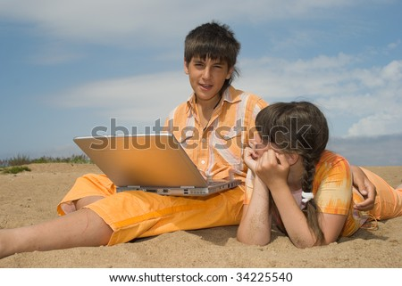 Two teens  (brother and sister) with laptops