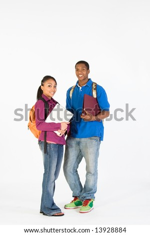 Two teens look ready for school with their backpacks, and notebooks. Vertically framed photograph