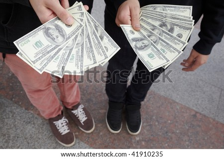 two teens staying with fans of dollars in their hands