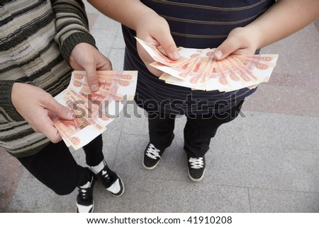 two teens staying with fans of russian rubles in their hands