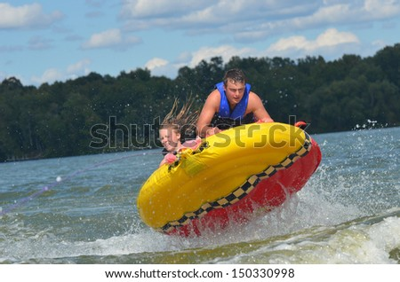 two teens tubing on a lake