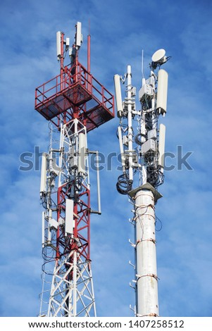 Two telecom cellular base station towers at blue sky with clouds