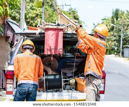 Two telecom engineer workers wearing orange uniform prepare stuff on a pick up car for field site working