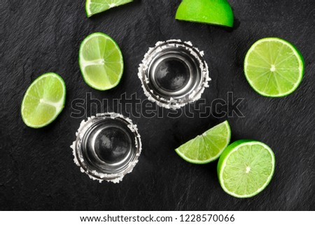 Two tequila shots with many lime slices, shot from the top on a dark background #1228570066