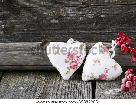 Two textile hearts with romantic flower coloring in simple dark wooden background with berries of red viburnum. selective Focus