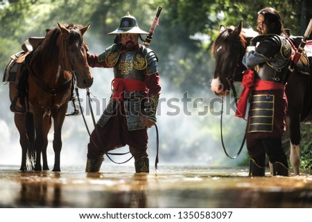 Two Thai warriors in ancient armor and horses standing in the water.Vintage Retro war costume concept.