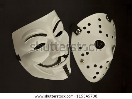Two theatrical looking white masks on a black background.