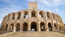 Two thousand year old amphitheater from Ancient Rome. The amphitheater in Arles is one of the best preserved. Heavy columns of white limestone stones. Large staircase at the foot of the building
