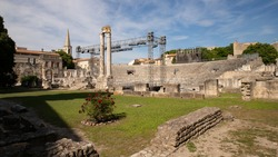 Two thousand year old theater from Ancient Rome. The theater in Arles is one of the best preserved. Heavy columns of white limestone stones. Large staircase and green lawn white blue sky